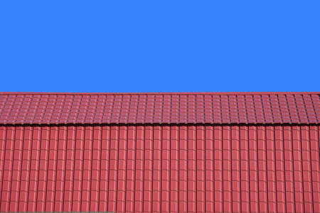 gable home renovation: Front view of new gable red house roof covered with metal tile isolated on blue background closeup Stock Photo