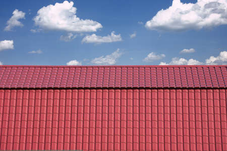 gable home renovation: Front view of new gable red cottage covered with metal tile closeup against blue sky with white clouds