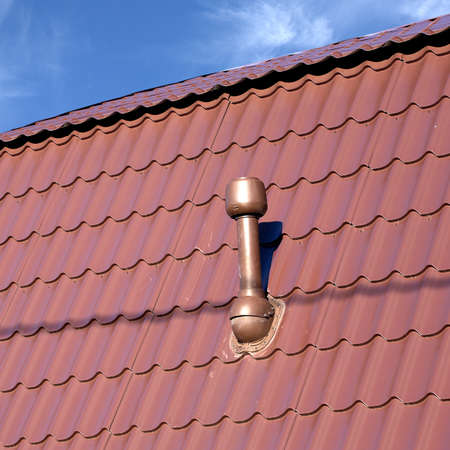 smokestack: Brown roof of a house covered with metal tile with short smokestack closeup against blue sky with white clouds