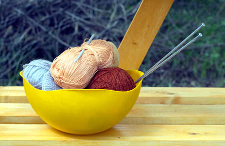 knitting needles: Color skeins of wool yarn, knitting needles and crochet hook in a big yellow bowl on wooden shelf outdoor. Photo closeup
