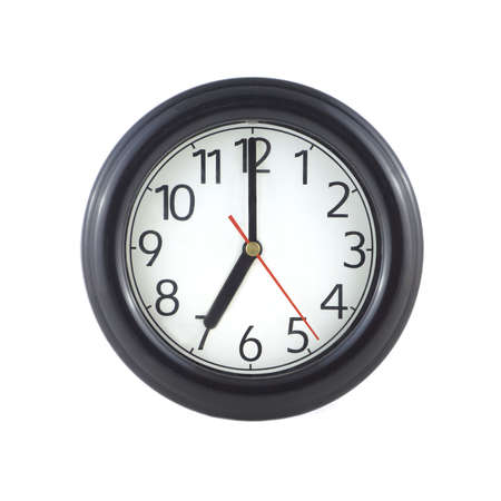 seven o'clock: Big round wall clock, with a dark rim on a white background close-up and arrows showing seven oclock Stock Photo