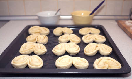pone: Preparing for baking small buns from doug. Twelve puffs on black tray in the kitchen closeup Stock Photo