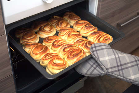 mitt: Hostess open oven door and takes the finished crunchy cakes holding tray with oven mitt. Side view closeup