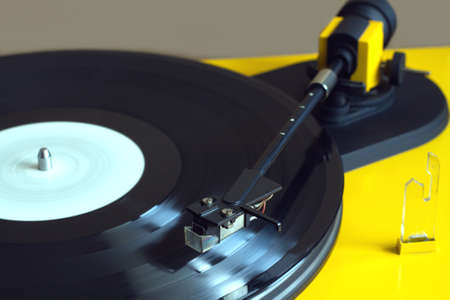 record player: Vinyl LP record with white label sound reproduction on vintage turntable record player with yellow case.