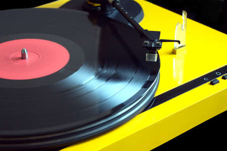 Vintage vinyl LP record with red label sound reproduction on vintage turntable record player with yellow case