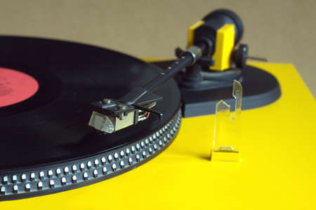hi fi: Turntable in yellow case playing a vinyl record with red label. Horizontal photo top view closeup Stock Photo