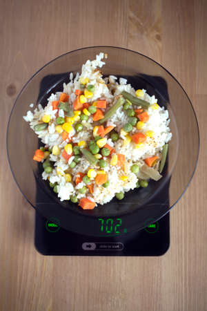 translucent white plate with rice and vegetables is at home kitchen
