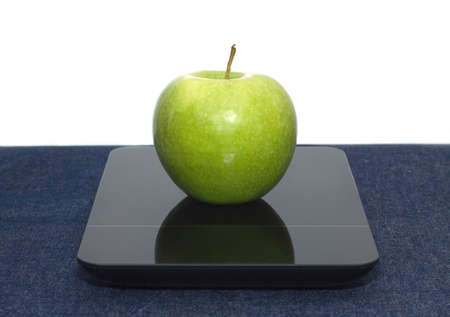 levis: Tasty green apple on kitchen scales on table covered jeans cloth against white background. Front view closeup
