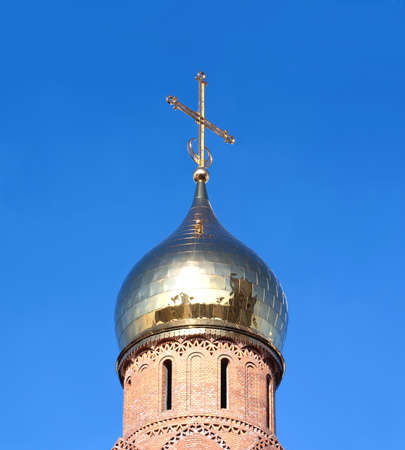cross section: Top of Christian church from red bricks with golden cupola over clear blue sky closeup