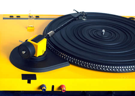 output: Turntable with black tonearm in yellow case with rubber mat on disc with stroboscope marks with output connectors rear view isolated on white background. Horizontal view closeup