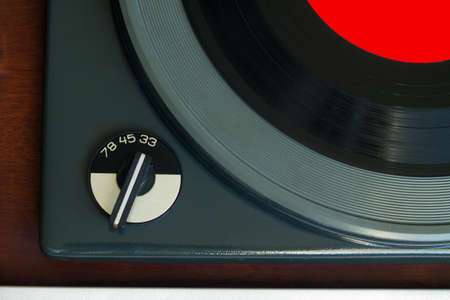 78 rpm: Part of vintage record player with wood finish and vinyl record with red label top view horizontal photo closeup