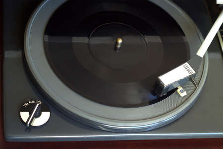 record player: Old vintage record player playing black flexible disc. Horizontal top view closeup