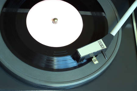 record label: Old vintage record player playing vinyl record with pink label. Horizontal top view closeup Stock Photo