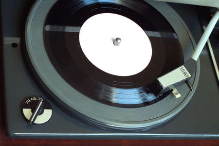 78 rpm: Old vintage record player playing vinyl record with pink label. Horizontal top view closeup Stock Photo