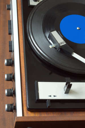 Old vintage record player playing vinyl record with blue label. Top view vertical photo view