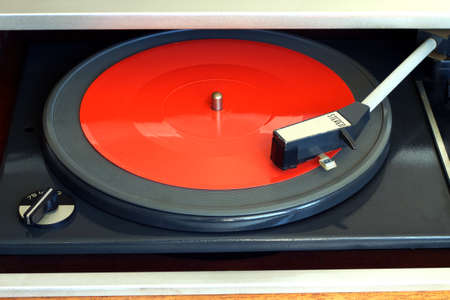 record player: Old vintage record player playing red flexible disc. Horizontal top view closeup