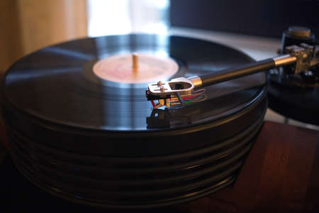 subdued: Vintage turntable rotating LP record in a room with subdued light. Horizontal view closeup Stock Photo