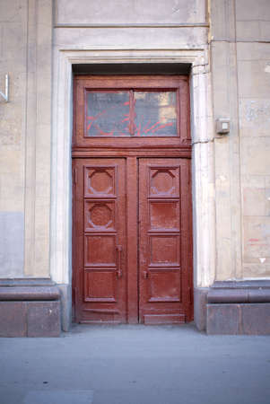 bad condition: Closed stone building door in bad condition painted brown color vertical front view closeup Stock Photo