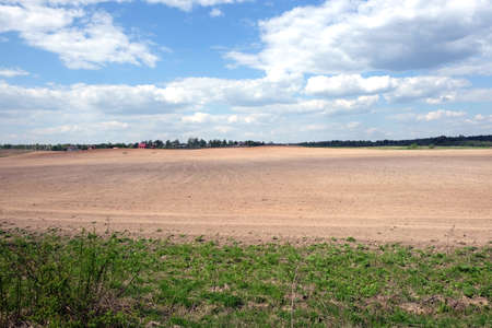 far away: Country landscape with plowed field and a village far away on spring day. Horizontal view