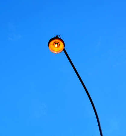 duskiness: City street lighting lamp lit at dusk on a long pole. Photo on blue cloudless sky in the evenong Stock Photo
