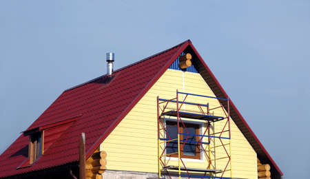 second floor: Yellow siding mounting on second floor country house made from wooden logs Stock Photo