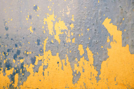 bad condition: Wall in bad condition with old yellow and blue paint inside house in process of repair as background closeup