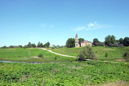 church ruins: Rural landscape with hills, river, a village and christian church ruins far away on sunny sumer day