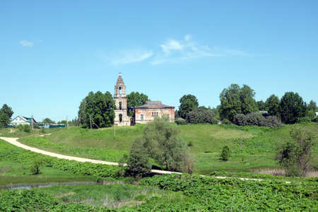 church ruins: Countryside landscape with hills, river, a village and christian church ruins far away on sunny summer day