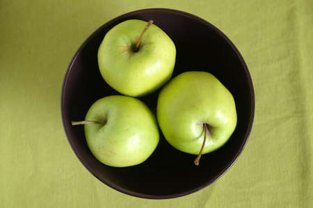 close up view: Three green apple inside purple bowl on green tablecloth top view close up