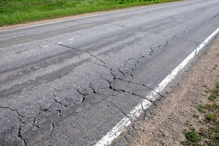 bad condition: Suburban road in bad condition needs repairs. Rural car road with broken asphalt in sunny summer day diagonal view Stock Photo