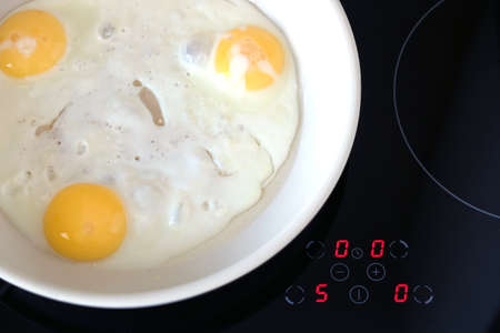 stove top: Breakfast. Three appetizing fried eggs in white pan on modern kitchen electric stove top view closeup Stock Photo