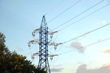 voltage gray: High-voltage power line metal prop with wires over cloudy blue sky in the evening horizontal view