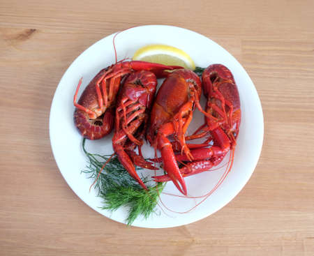 Boiled crayfish color with lemon and dill lie on a round white plate on a wooden table surface. Top view close-up