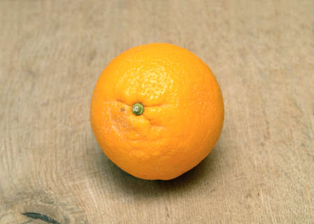 stilllife: Still-life with ripe orange on brown wooden surface front view horizontal closeup
