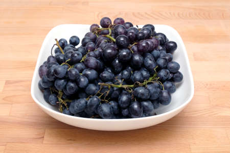 stilllife: Still-life with lot of ripe wine grape bunches with black berries in square bowl on wooden white background close up