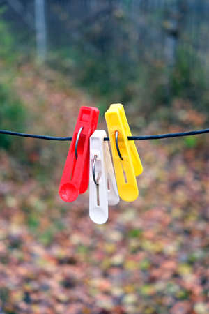 clothespegs: Three colored clothespins hanging on black rope on a blurred background in autumn day outdoors vertical view closeup