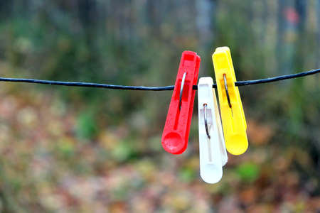 clothespegs: Three colored clothespins hanging on black rope on a blurred background in autumn day outdoors horizontal view closeup