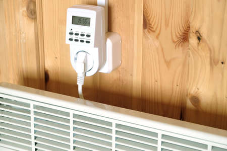 power operated: Working white electric convector heater plugged to timer power socket operated in smart house system against wooden wall inside room side view closeup