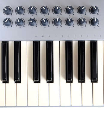 octave: Fragment of electronic synthesizer keyboard with many control buttons isolated on white background top view closeup