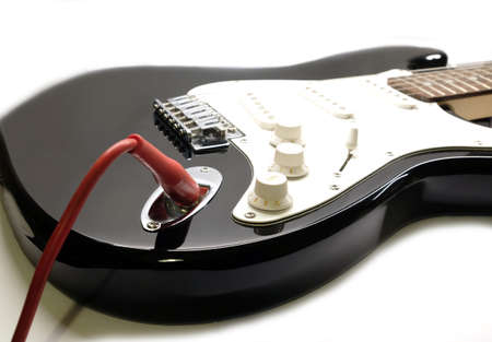 Part of modern electric six string guitar black color with glossy finish with red cord in socket, pickups and control knobs isolated on white background horizontal view close up