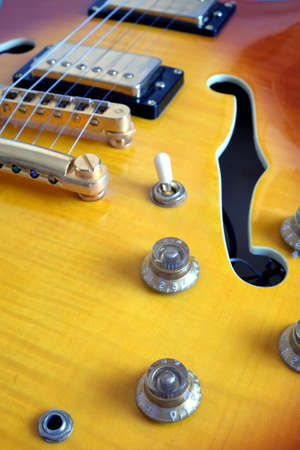 Part of vintage semi-hollow body electric guitars with pickups, electronics knobs and metal accessories closeup Stock Photo