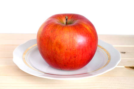Big ripe red apple on white plate with gold trim in beige wooden shelf on white background front view closeup