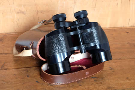 Vintage Porro prism black color binoculars and opened brown leather case on wooden background side view closeup