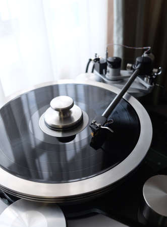 Tonearm of vintage turntable with LP record close up view