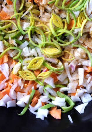 Still life with cutted carrots, onion, leek and fragrant spices on kitchen cast iron pan before frying as background vertical view close up Stock Photo
