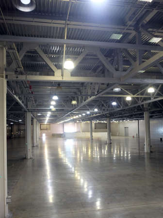 Large empty warehouse interior in an industrial building with high vertical columns and with high ceiling and artificial lighting Редакционное