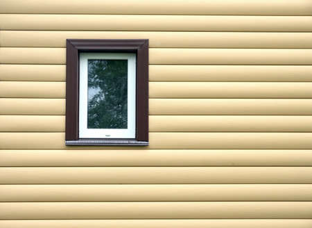close up: Building wall finished with beige siding panels with small vertical plastic window Stock Photo