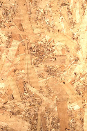 OSB panel. Rear side view. Chipboard building material made of pressed sandy brown wood shavings as background