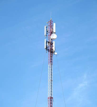 晴れた日の青空の上のアンテナで高の赤と白の携帯電話タワー 写真素材
