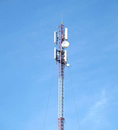 High red and white cellular tower with aerials on top over clear blue sky in sunny day